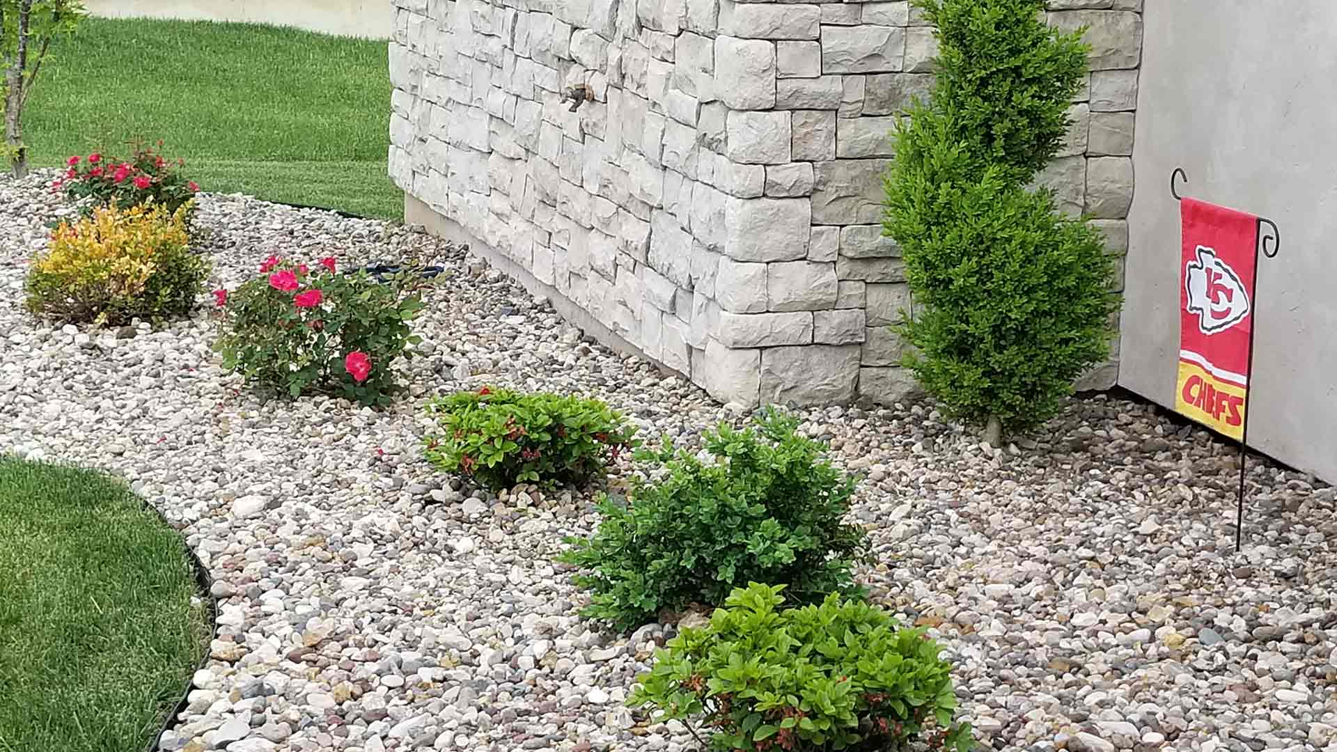 Ground covering by McVey Mowing at Columbia, MO home's front yard with flowers and river gravel.