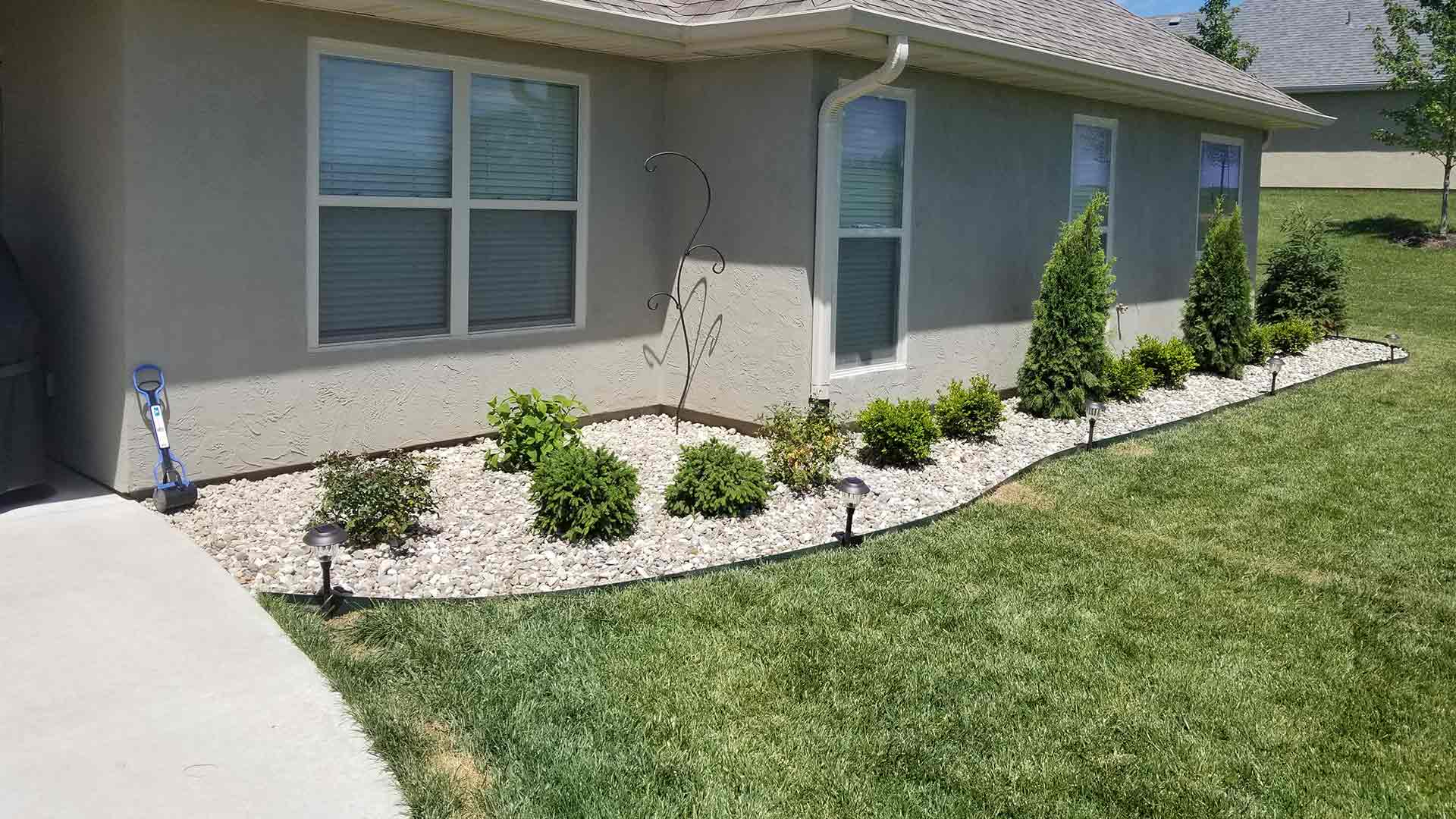 Columbia, MO home with freshly pruned bushes and rock installed by McVey Mowing.